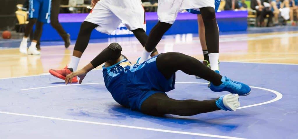 Basketball player falls on court