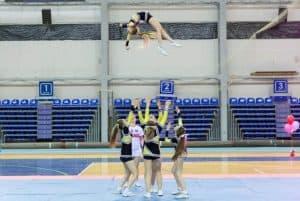 Cheerleader being thrown in the air