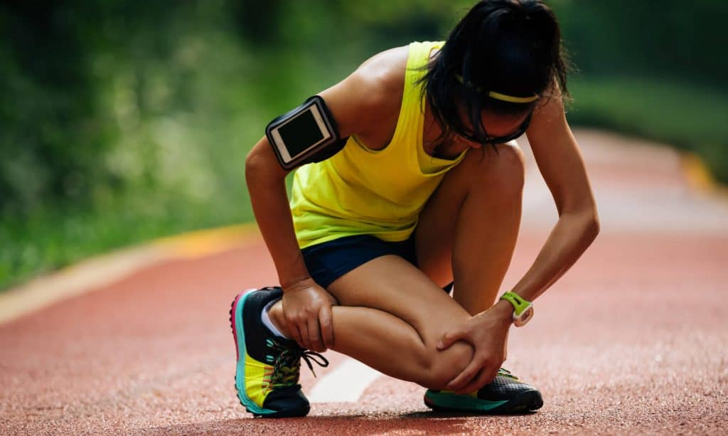 Female runner suffering with pain on sports running knee injury